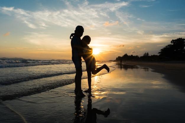Silhouette di fratelli che abbracciano sulla spiaggia