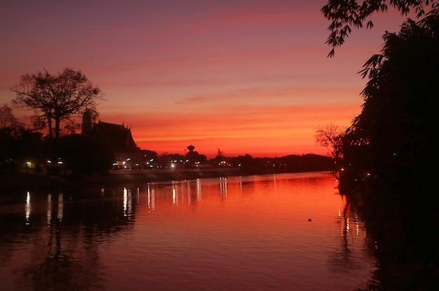 Silhouette di un tempio buddista sulla riva del fiume chao phraya con un fantastico colore vivido del cielo al tramonto