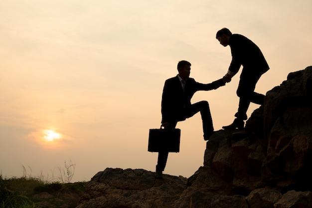 Silhouette di un uomo d'affari che si aiuta a vicenda a scalare una montagna al tramonto, concetto di successo del lavoro di squadra d'affari.
