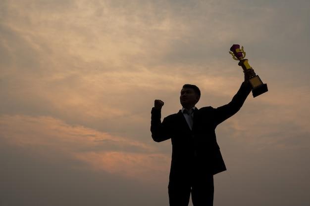 Siluetta dell'uomo d'affari in piedi sulla montagna con in mano una coppa trofeo, un concetto di successo e leadership.