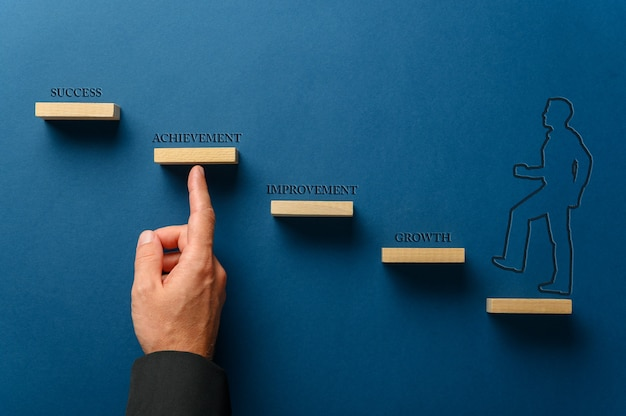 Sagoma di un uomo d'affari che cammina sui gradini verso il successo in un'immagine concettuale. su sfondo blu.