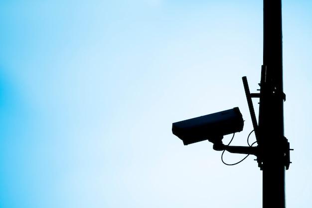 Silhouette di una telecamera cctv con uno sfondo blu.