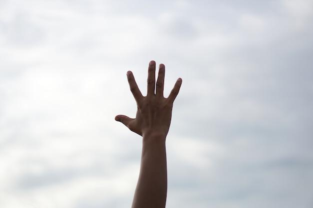 Silhouette di preghiere cristiane che alzano la mano mentre pregano il dio