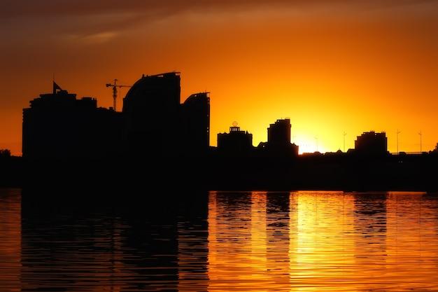Siluetta della città al tramonto che riflette nel fiume