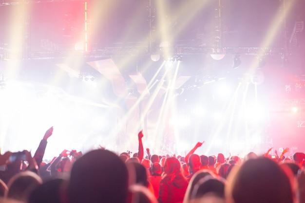 Siluetta di una folla di concerto. il pubblico guarda verso il palco. persone in festa a un concerto rock. festa musicale. spettacolo musicale. sagoma di gruppo. pubblico giovane.