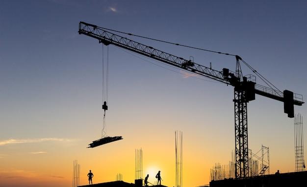 Profili il materiale di sollevamento della gru da costruzione sul cantiere e sui lavoratori sul cielo al tramonto