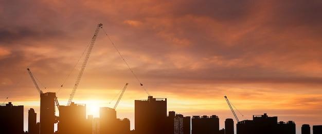 Profili il controllo dei lavori di costruzione e lo sfondo della gru a torre sul cielo al tramonto naturale