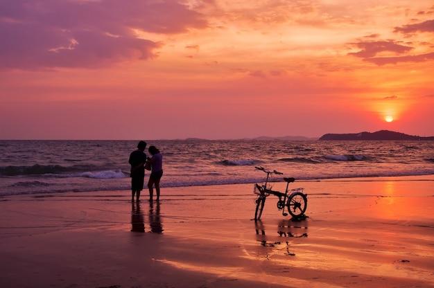 Siluetta delle coppie che stanno sulla spiaggia con il cielo drammatico di tramonto