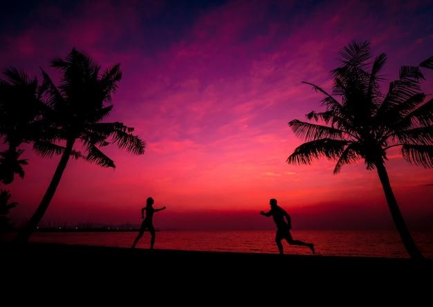 Siluetta delle coppie sulla spiaggia tropicale durante il tramonto su fondo delle palme