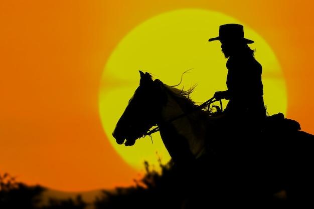 La silhouette del cowboy e il sole al tramonto