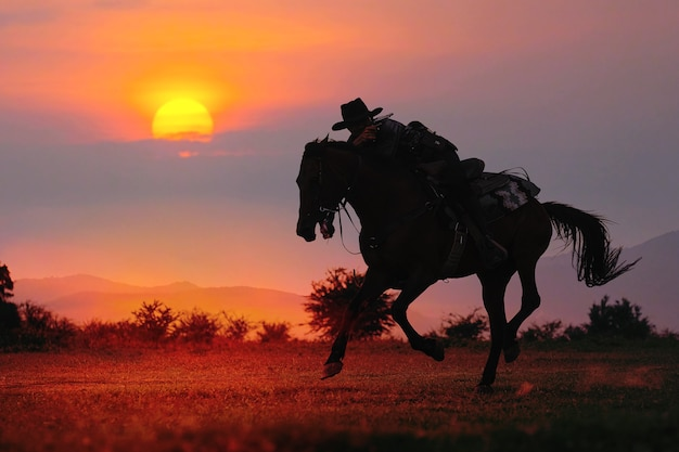 La silhouette del cowboy e il sole al tramonto Foto Premium