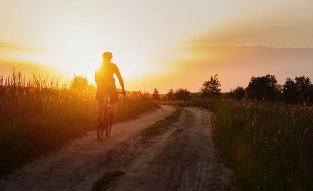 Siluetta del ciclista su una bici di ghiaia che guida su un sentiero di polvere al tramonto.