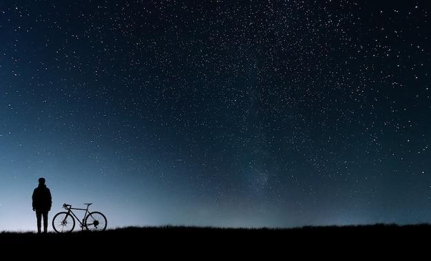 Sagoma di un ciclista con una bicicletta in piedi vicino al cielo stellato.
