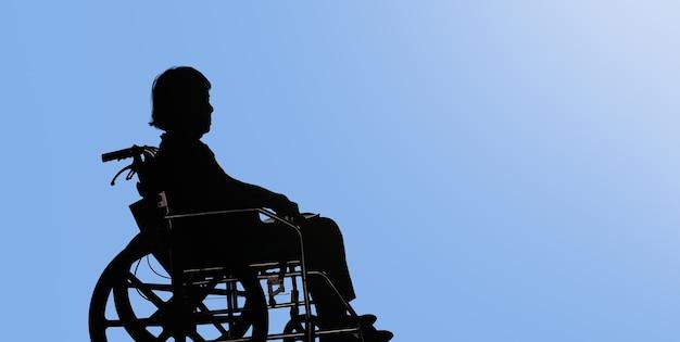 Silhouette di donna anziana disabile e abbattuta seduta nella sua sedia a rotelle