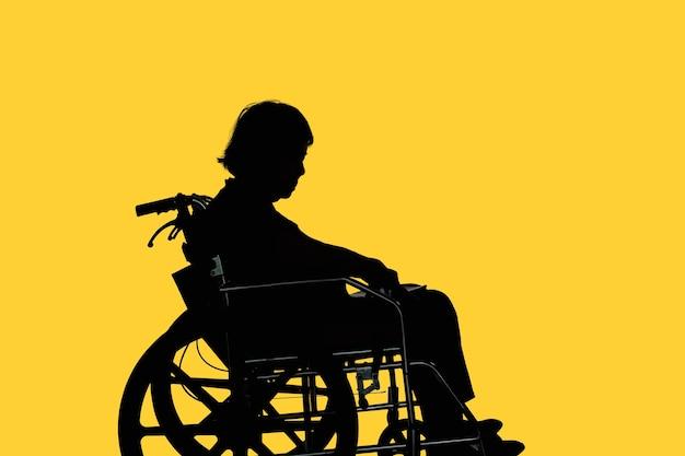 Silhouette di donna anziana disabile e abbattuta che si siede sulla sua sedia a rotelle
