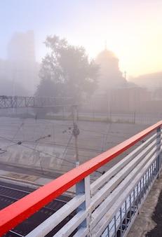 La sagoma della cupola del tempio nella foschia, la ringhiera rossa del ponte pedonale. siberia, russia