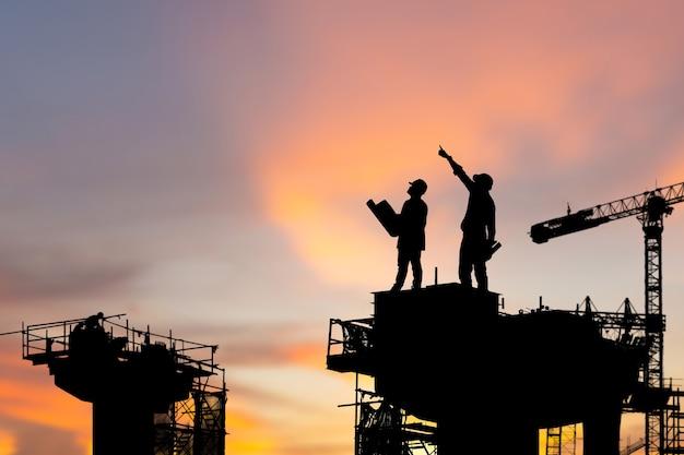 Siluetta dell'ingegnere e del lavoratore che controllano il progetto sullo sfondo del cantiere, cantiere dell'infrastruttura al tramonto in orario serale