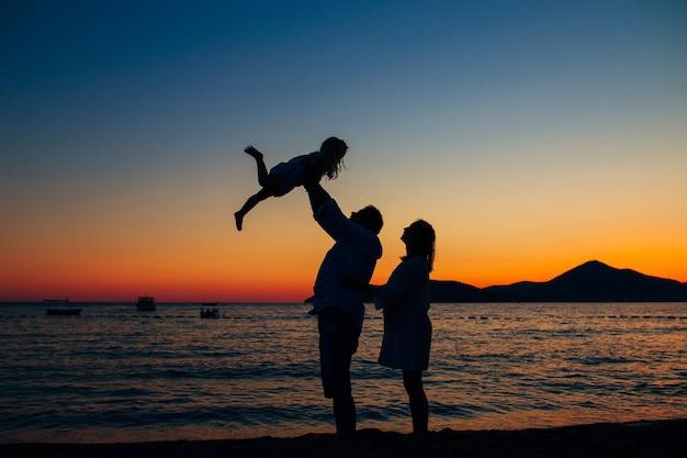 Silhouette di una famiglia con bambini sullo sfondo del sole e del mare al tramonto
