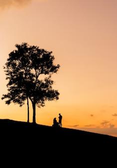 Sagoma di padre, madre e figlia che giocano al tramonto in tempo serale
