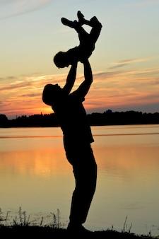 Silhouette di un padre che gioca con il bambino sullo sfondo del tramonto