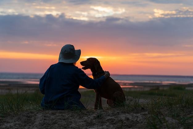 Silhouette di una femmina che abbraccia il cane vizsla e godersi il cielo del tramonto insieme amore per il concetto di animali domestici