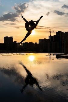 Siluetta della ballerina flessibile femminile che salta durante il tramonto sullo sfondo del paesaggio urbano con la riflessione i...