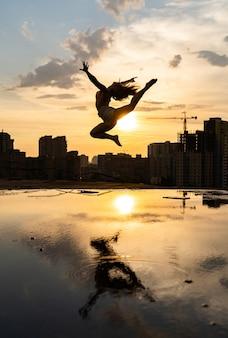 Siluetta della ballerina flessibile femminile che salta durante il tramonto sul fondo di paesaggio urbano con la riflessione nell'acqua