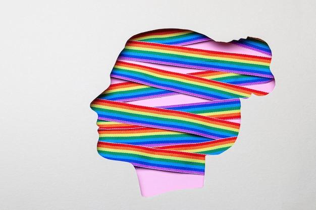 Siluetta di una testa femminile e nastri arcobaleno di orgoglio lgbt. lesbiche in testa.