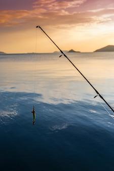 Siluetta del pescatore che pesca sulla spiaggia al tramonto