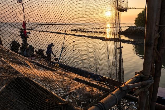 Silhouette pescatore e molti pesci in barca al molo durante il tramonto, bang pu, samuth prakan, thailandia. industria dei frutti di mare.