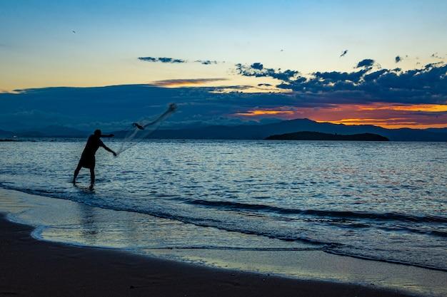 Sagoma di un pescatore che getta la rete da pesca