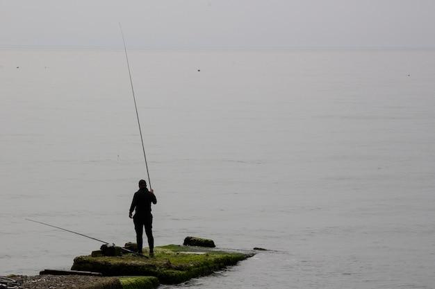 Sagoma pescatore con canna da pesca alla luce del sole dell'alba, uomo di contorno godersi lo sport hobby sul lago serale, persona pescare nel cielo notturno, concetto di pesca relax