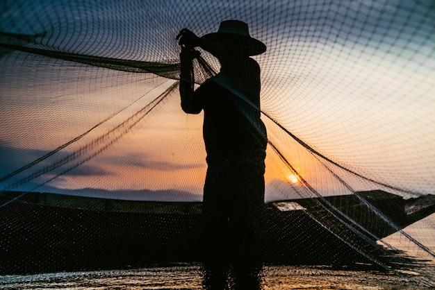 Sagoma di pescatori utilizzando strumenti di pesca e durante il sole dorato splende