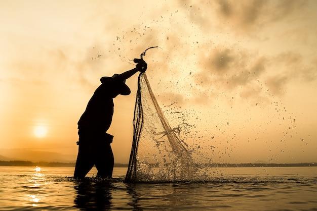 Sagoma di pescatori utilizzando strumenti di pesca e durante il sole dorato splende Foto Premium