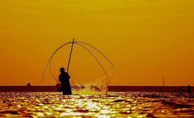 Silhouette di pescatori che usano attrezzi da pesca e durante il sole dorato splende