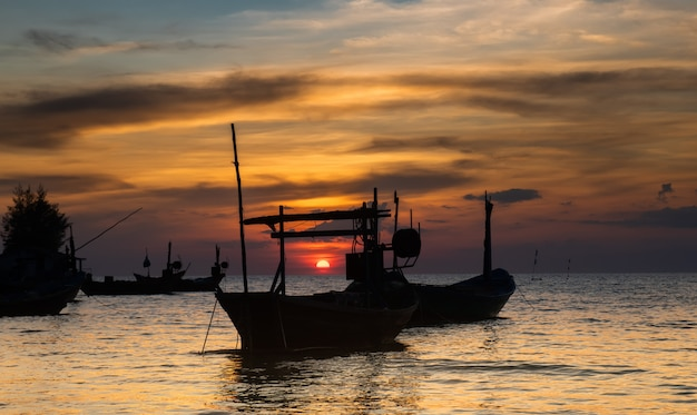 Siluetta della barca di legno della pesca sul mare