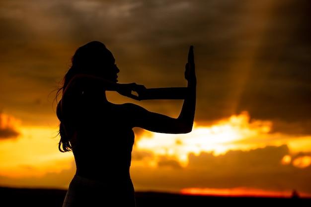 Silhouette di una donna fitness che si allunga al tramonto con il sole sullo sfondo
