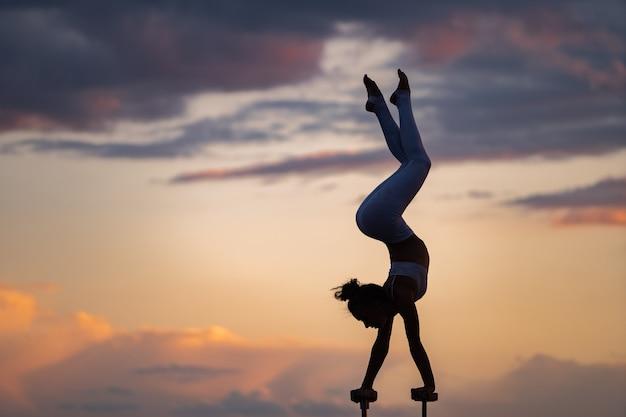 Siluetta della ragazza flessibile e in forma che fa la verticale e mantiene l'equilibrio contro il drammatico disagio