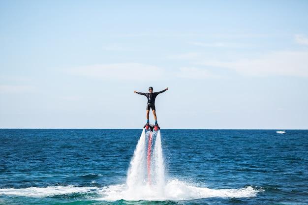 Silhouette di un pilota di fly board in mare