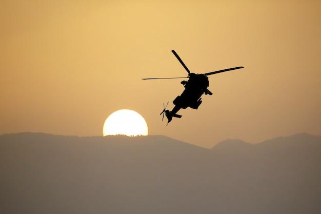 Silhouette di un elicottero in volo contro il sole al tramonto