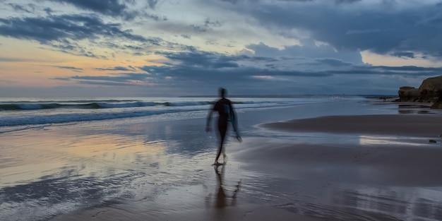 Profili il surfista della forma sulla vista sul mare del fondo al tramonto. portogallo.