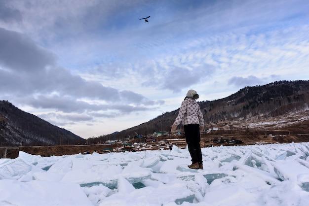 Siluetta della vista posteriore della ragazza guardando il cielo su un parapendio in volo rimane su un mucchio di bellissimi cumuli di ghiaccio vicino alla vecchia ferrovia circum baikal in inverno.