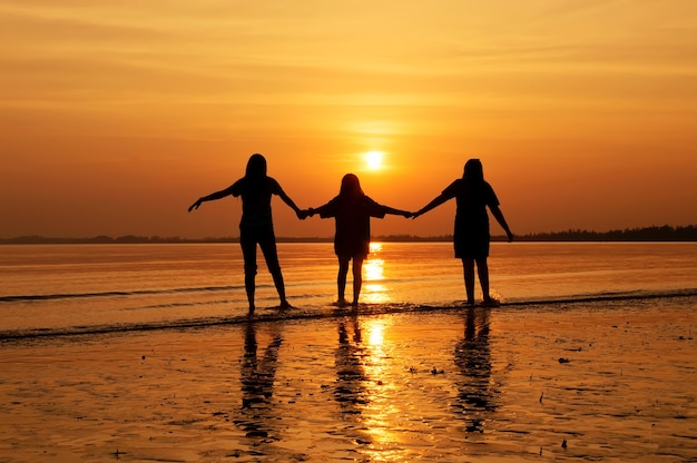 Siluetta della mano della holding del gruppo della ragazza che cammina sulla spiaggia al tramonto