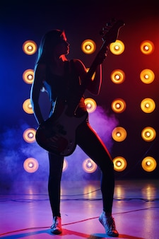 Ragazza della siluetta con una chitarra in mano sul palco che canta una canzone in stile rock