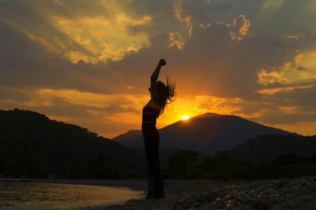 Siluetta di una ragazza con i capelli che cadono dalle sue mani in piedi in riva al mare nei raggi del tramonto. i raggi di sole arancioni irrompono tra le montagne.