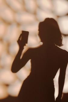 Sagoma di donna graziosa che cattura un selfie Foto Premium
