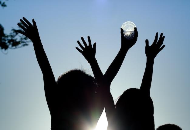 Silhouette, gruppo di bambini felici che giocano sulla priorità bassa di tramonto.