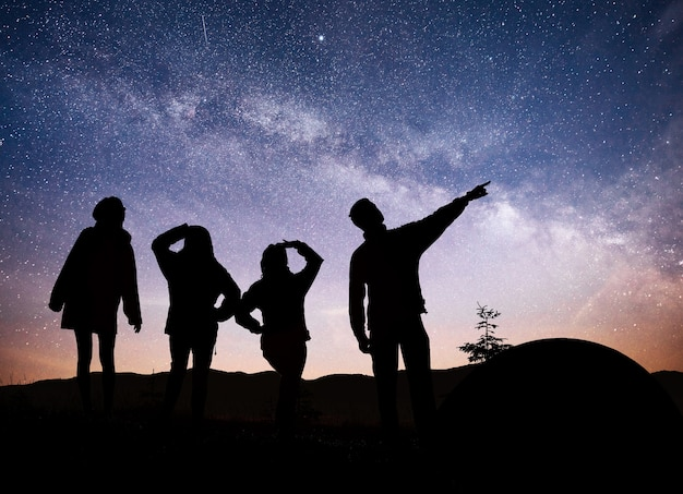 Una silhouette di persone di gruppo si diverte in cima alla montagna vicino alla tenda durante lo sfondo della via lattea su un tono luminoso del cielo stellato.