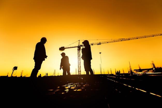Gruppo silhouette di lavoratore e ingegnere civile in uniforme di sicurezza installare acciaio rinforzato