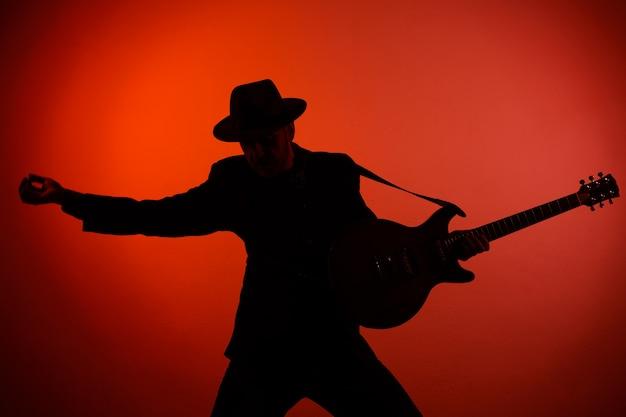 Siluetta del chitarrista in un cappello sul rosso